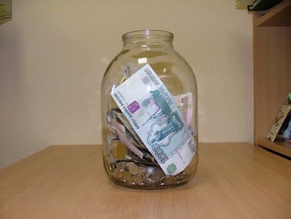 стеклянная банка с монетами и купюрами