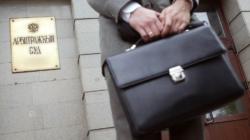 человек с портфелем на фоне арбитражного суда
