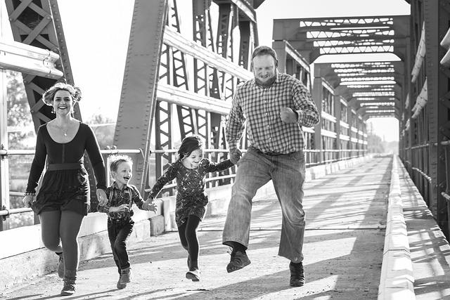 мужчина женщина мальчик и девочка радостные бегут по мосту